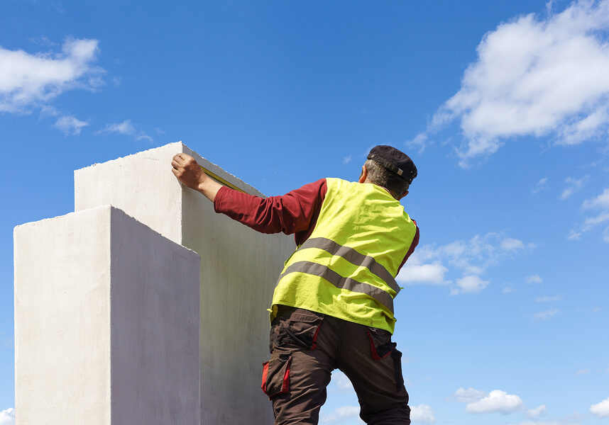 a man measuring the white chimney